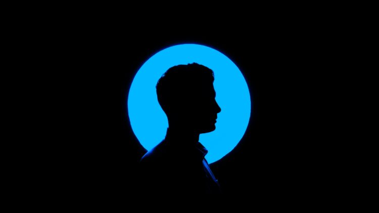 Silhouette of a man in front of a blue circular light.