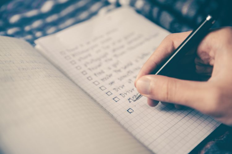Picture of someone handwriting a list in a notepad