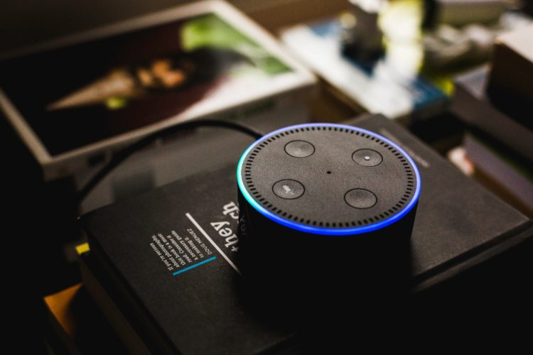 Amazon Dot with Alexa voice assistance sitting on top of books