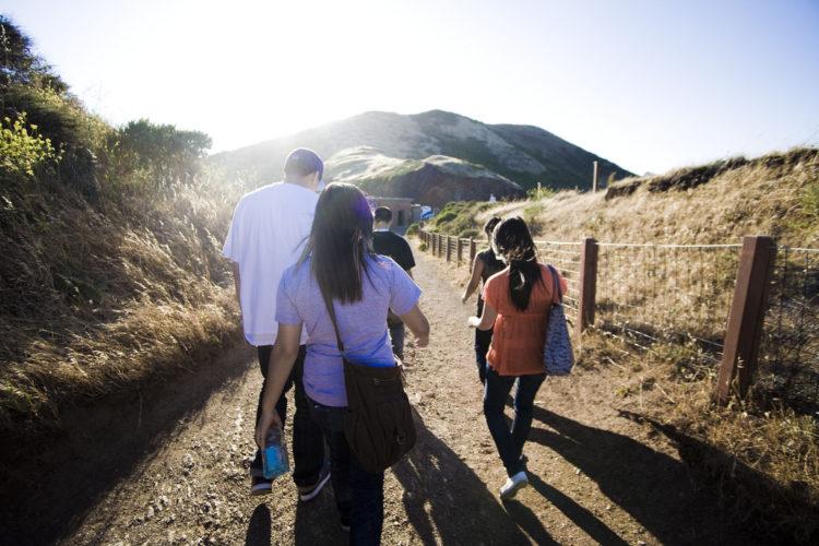 Tourists walking on a dirt path to a tourist destination