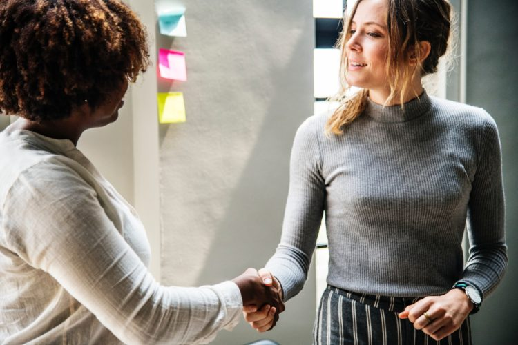 Two business women shake hands during a meeting