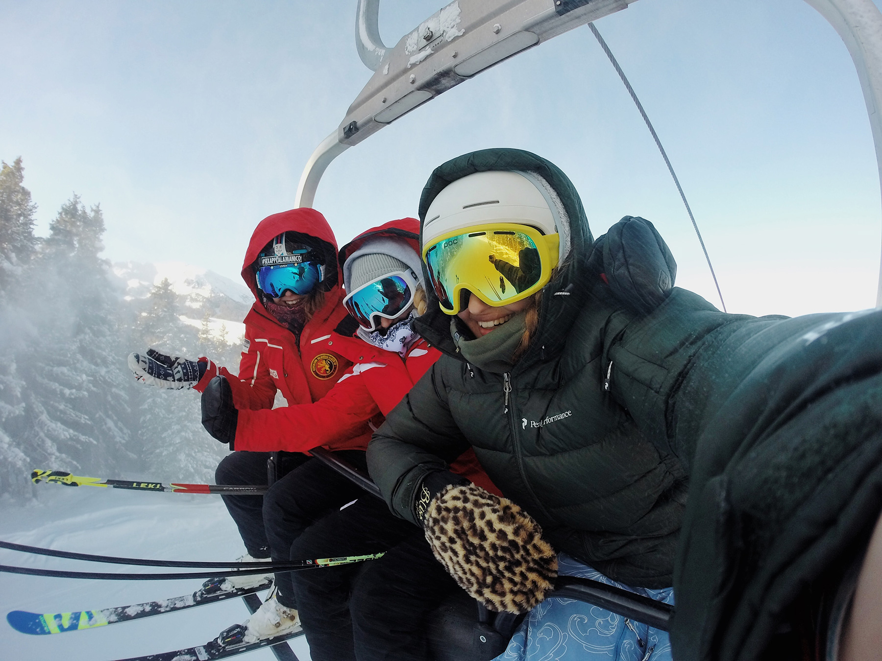 Three skiers taking a selfie while on the lift.