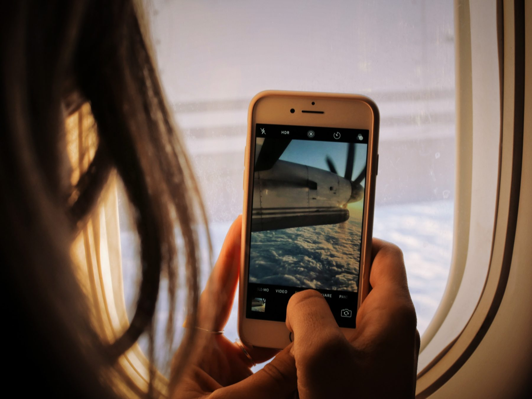 Closeup of a woman taking a picture through her airplane window while flying